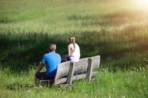 dwie osoby siedzące na ławce